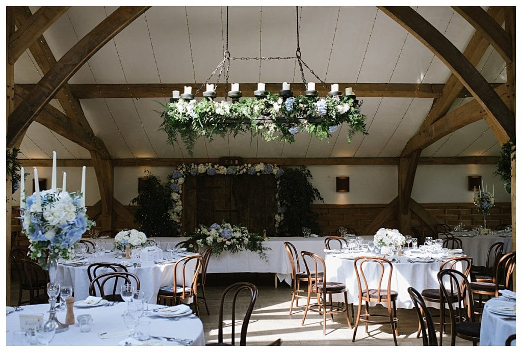 Chandelier at Cripps Barn decorated with foliage and flowers