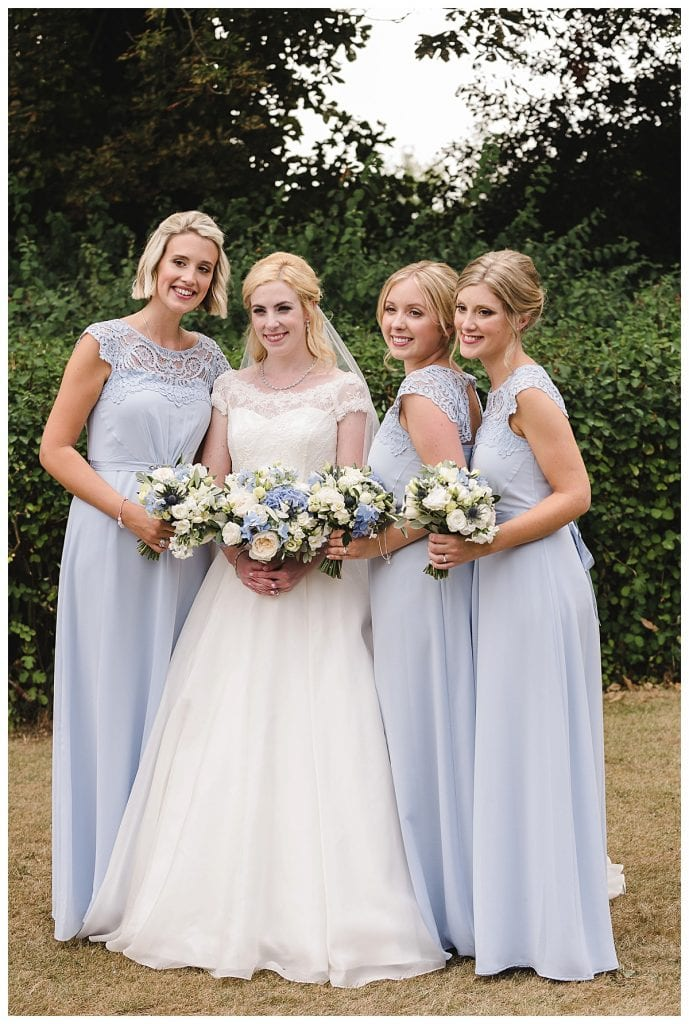 Bride and her bridesmaids wearing elegant pale blue dresses holding their wedding bouquets