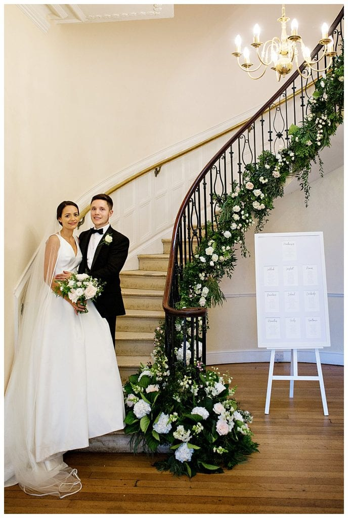 Bride and groom standing on the stairs at Eastington Park
